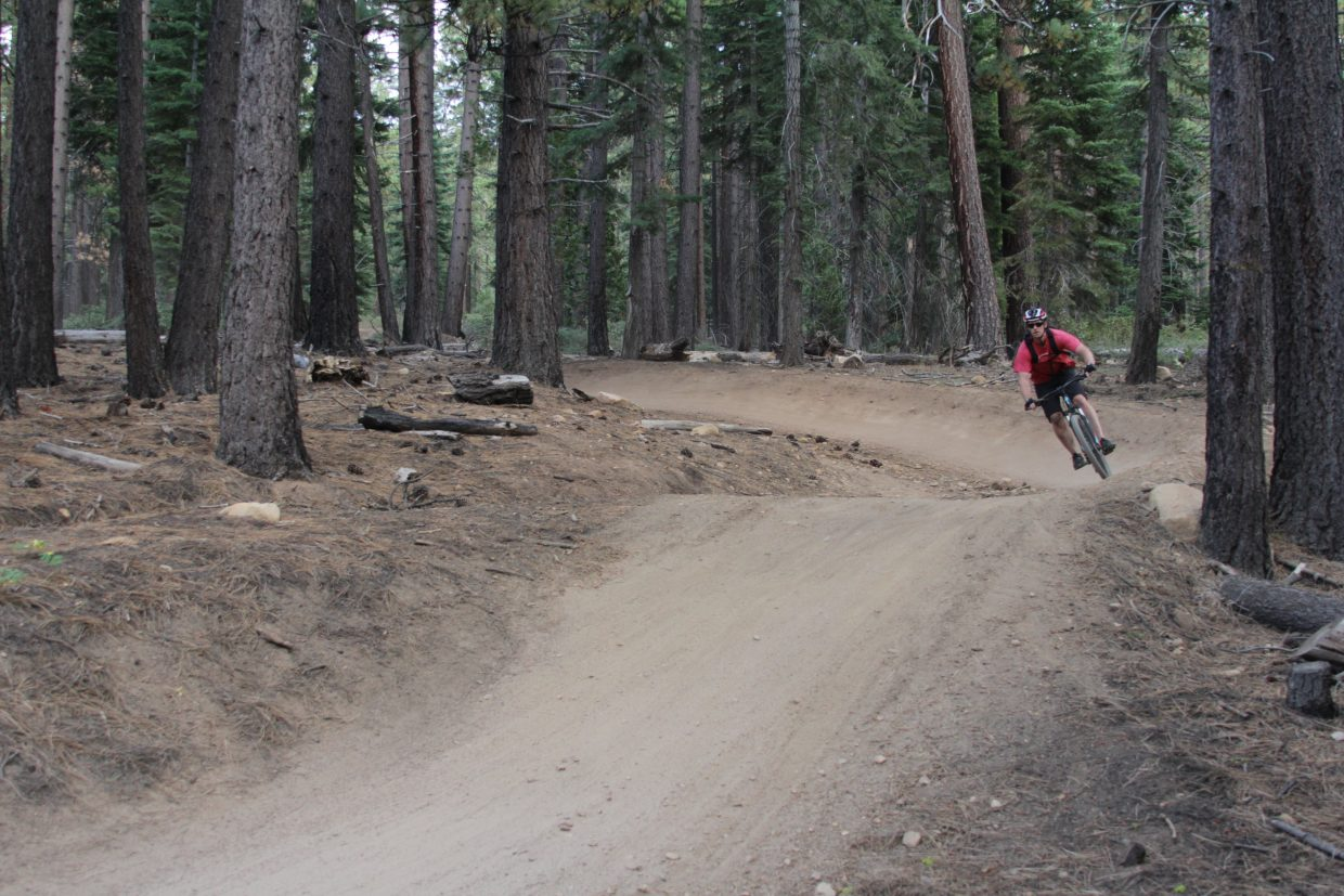 A biker cruises through a curve on the Corral Trail.