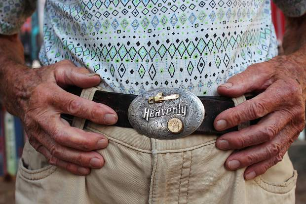 A friend gifted Hollay this custom belt buckle, which depicts a chainsaw and a tree stump with an
