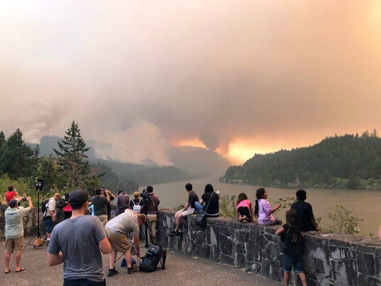 This Sept. 4, 2017, photo provided by Inciweb shows people at a viewpoint overlooking the Columbia River watching the Eagle Creek wildfire burning in the Columbia River Gorge east of Portland, Ore. A lengthy stretch of highway Interstate 84 remains closed Tuesday, Sept. 5, 2017, as crews battle the growing Eagle Creek wildfire that has also caused evacuations and sparked blazes across the Columbia River in Washington state. (Inciweb via AP)