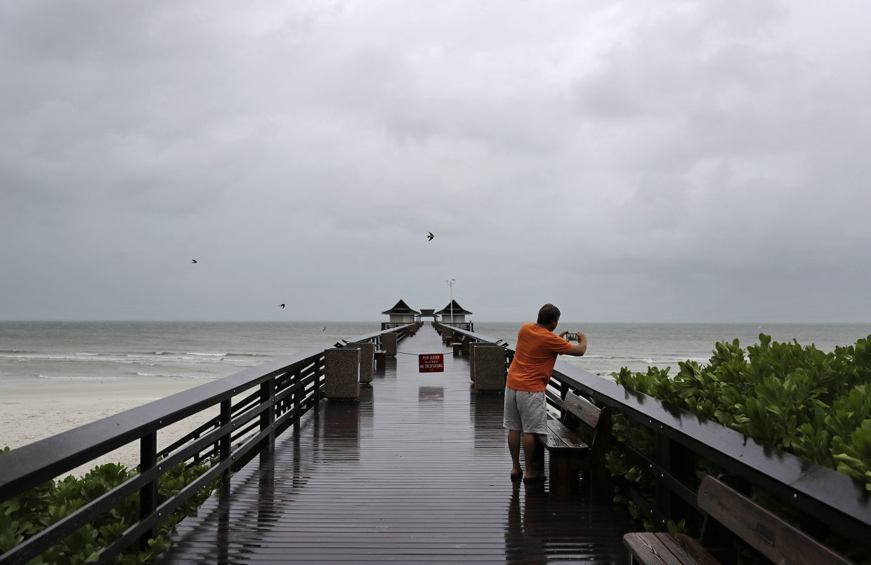 Keith Gahagan takes a photo of the early effects of Hurricane Irma in Naples, Fla., Sunday, Sept. 10, 2017. Gahagan plans on riding out the storm in Naples but on higher ground further inland. (AP Photo/David Goldman)