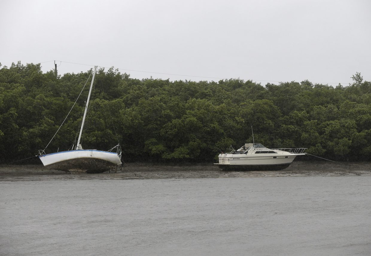 Two boats that are moored sit in mud due to an unusually low tide, as the first effects of Hurricane Irma reach Fort Myers, Fla., Sunday, Sept. 10, 2017. Announcing itself with roaring 130 mph winds, Hurricane Irma plowed into the mostly emptied-out Florida Keys early Sunday. (AP Photo/Gerald Herbert)
