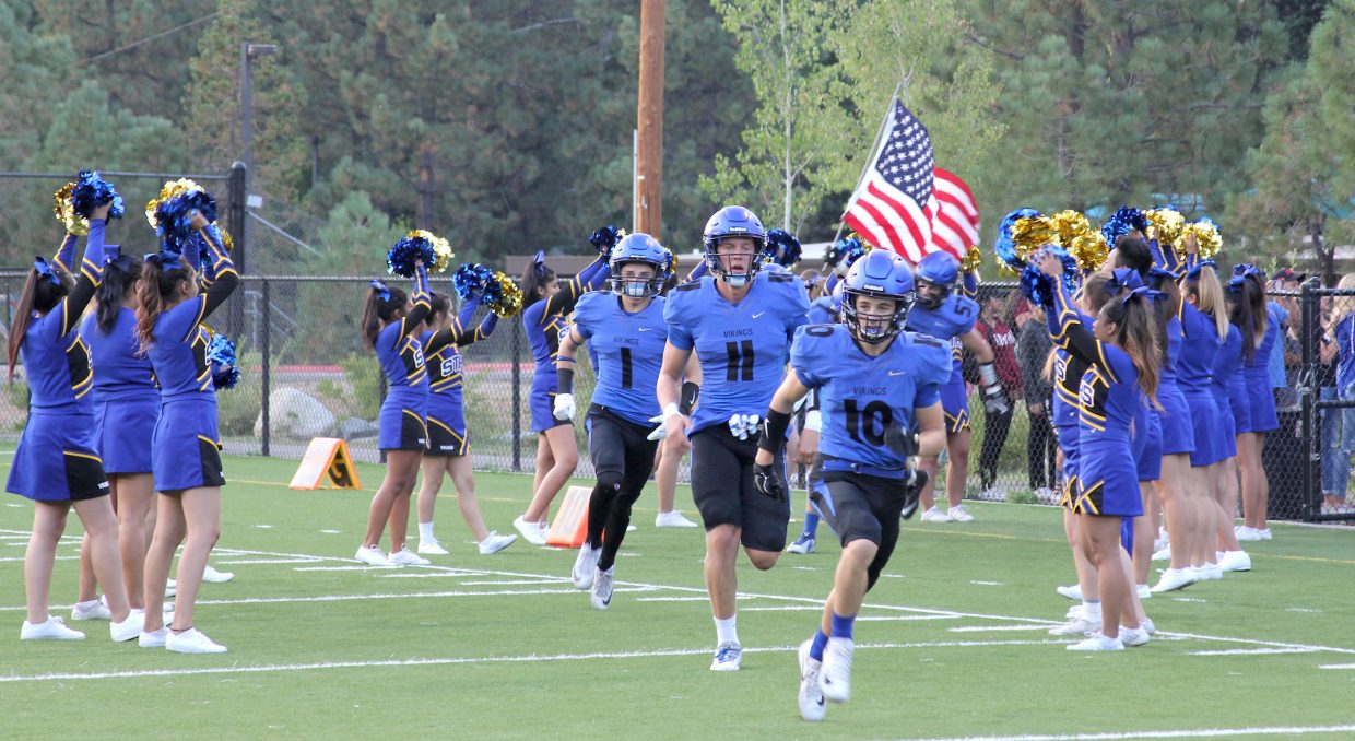 Kody Griffis (10) and Mccallan Castles lead South Tahoe onto the field Friday night.