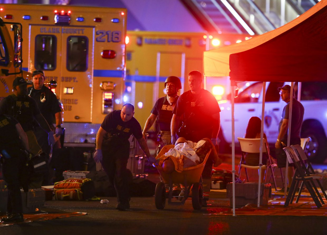 A wounded person is walked in on a wheelbarrow as Las Vegas police respond during an active shooter situation on the Las Vegas Stirp in Las Vegas Sunday, Oct. 1, 2017. Multiple victims were being transported to hospitals after a shooting late Sunday at a music festival on the Las Vegas Strip.