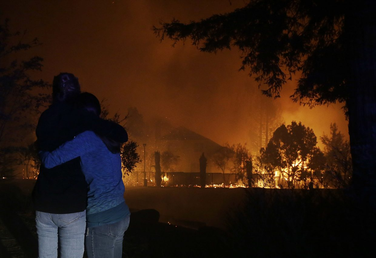 Two women hug as they watch houses burn in Santa Rosa, Calif., Monday, Oct. 9, 2017.