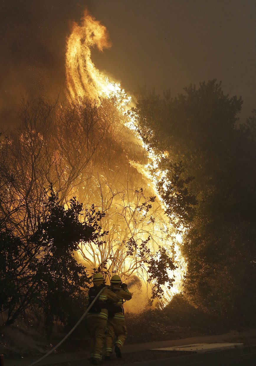 Firefighters hose down a burning tree in Santa Rosa, Calif., Monday, Oct. 9, 2017. Wildfires whipped by powerful winds swept through Northern California early Monday, sending residents on a headlong flight to safety through smoke and flames as homes burned.