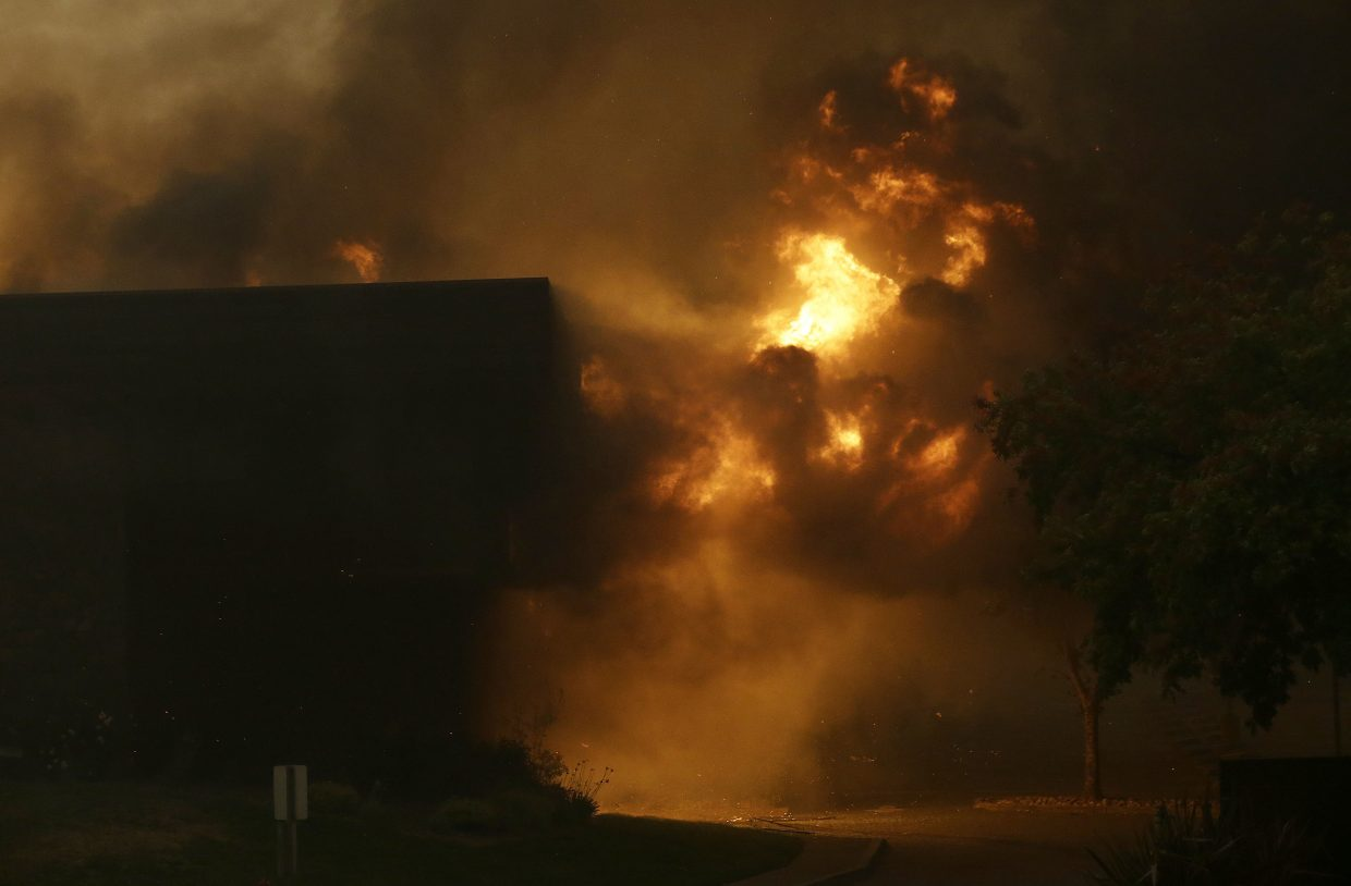 Smoke and fire rise from the Fountaingrove Inn Hotel as it burns in Santa Rosa, Calif., Monday, Oct. 9, 2017. Wildfires whipped by powerful winds swept through Northern California early Monday, sending residents on a headlong flight to safety through smoke and flames as homes burned.