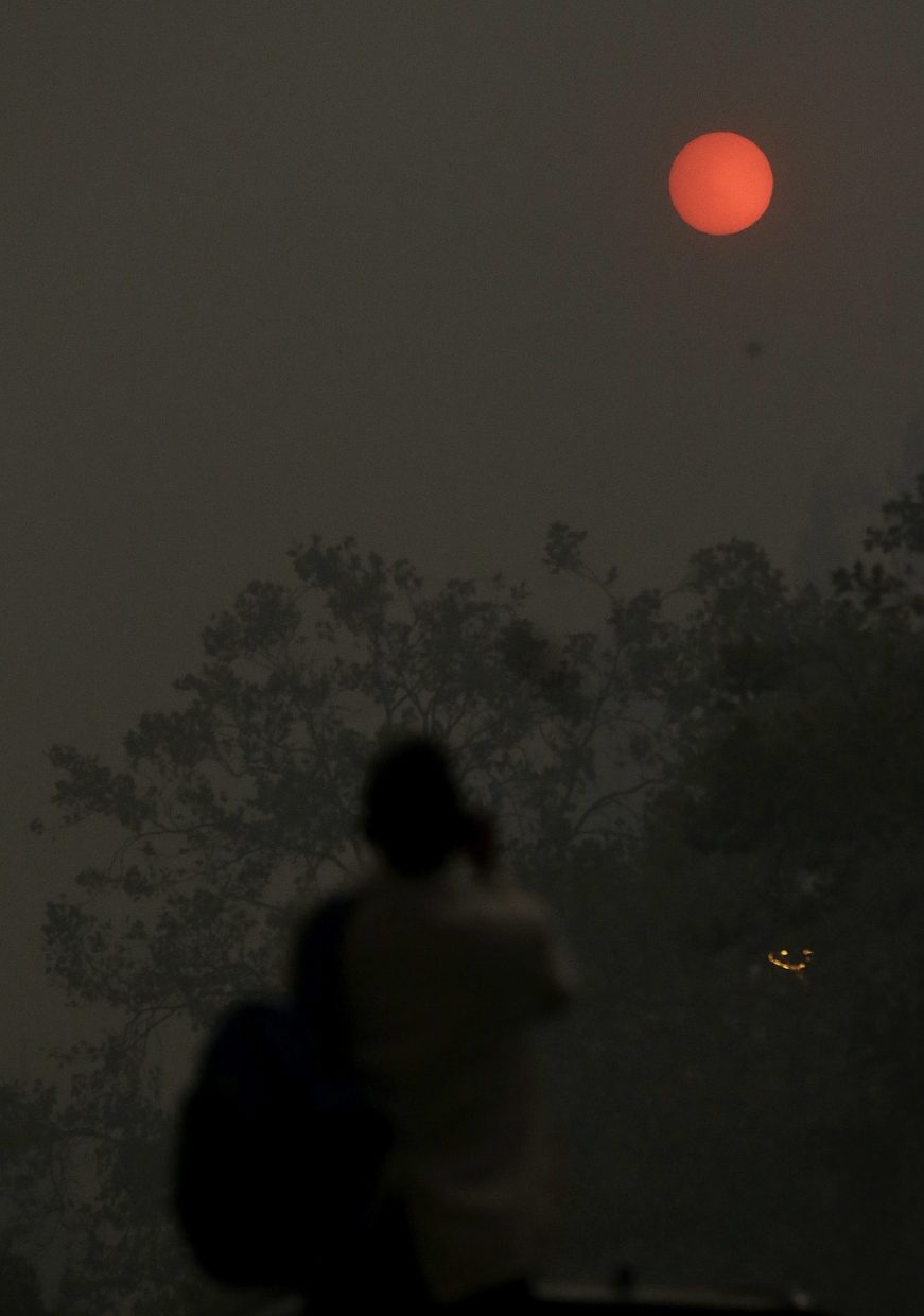 A woman takes a photo of the sun covered from smoke and haze from fires in Santa Rosa, Calif., Monday, Oct. 9, 2017. Wildfires whipped by powerful winds swept through Northern California early Monday, sending residents on a headlong flight to safety through smoke and flames as homes burned.