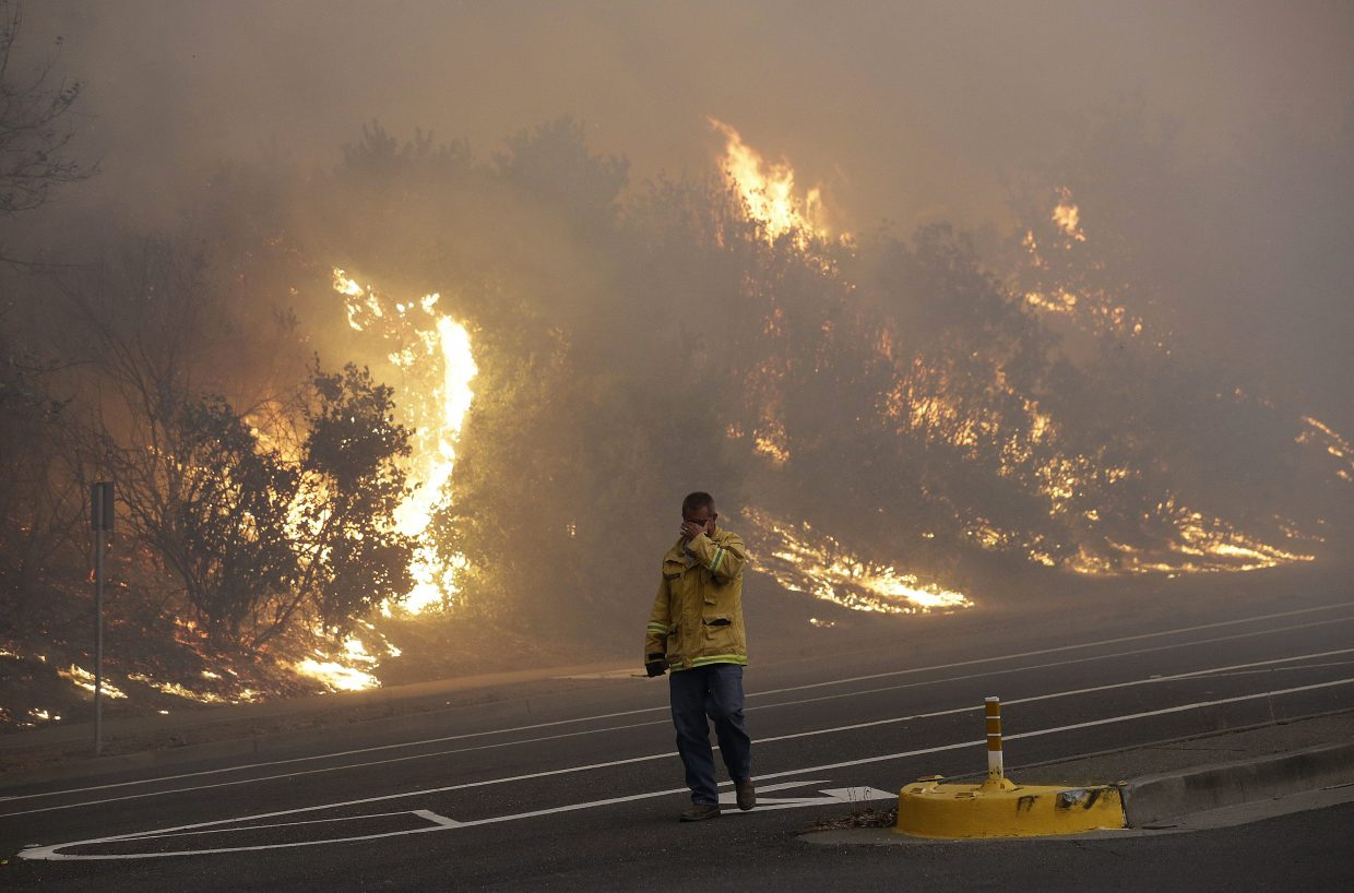 A firefighter covers his eyes as he walks past a burning hillside in Santa Rosa, Calif., Monday, Oct. 9, 2017. Wildfires whipped by powerful winds swept through Northern California, sending residents on a headlong flight to safety through smoke and flames as homes burned.
