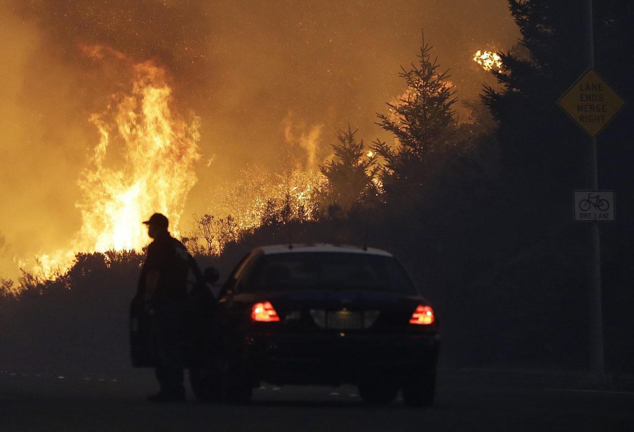 A law enforcement officer blocks a road as flames burn in a residential area in Santa Rosa, Calif., Monday, Oct. 9, 2017. Wildfires whipped by powerful winds swept through Northern California early Monday, sending residents on a headlong flight to safety through smoke and flames as homes burned.