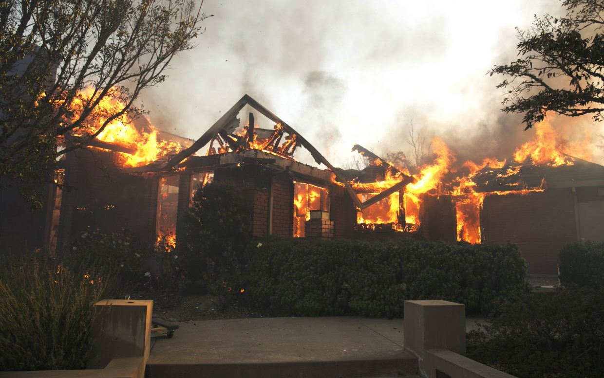 Flames from a wildfire consume a home Monday, Oct. 9, 2017, east of Napa, Calif. Wildfires whipped by powerful winds swept through Northern California early Monday, sending residents on a headlong flight to safety through smoke and flames as homes burned.