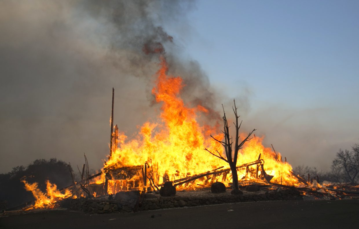 Flames from a wildfire consume a home Monday, Oct. 9, 2017, east of Napa, Calif. The fire is one of several burning across Northern California's wine country.