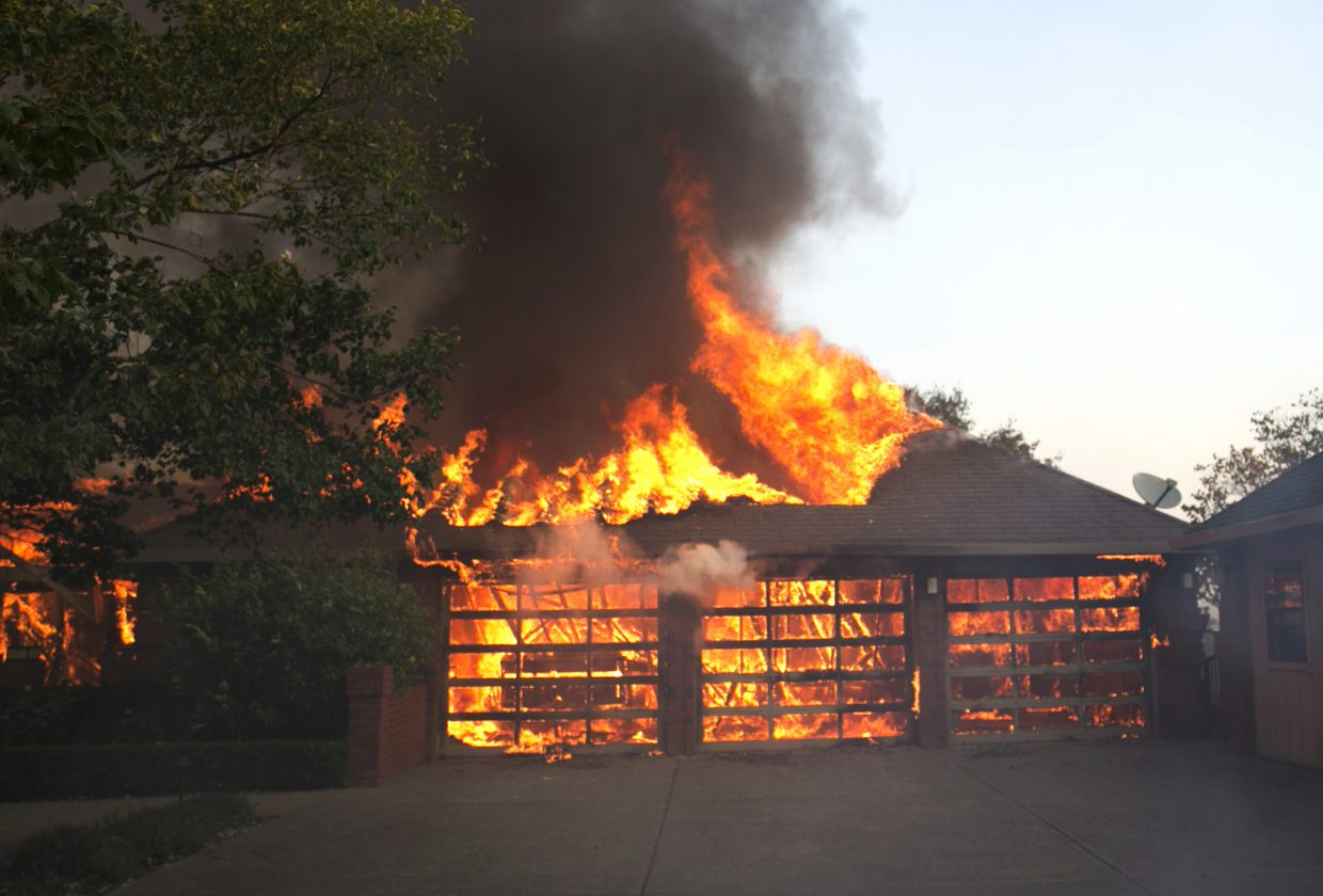 Flames from a wildfire consume a a three car garage at a home Monday, Oct. 9, 2017, east of Napa, Calif. Wildfires whipped by powerful winds swept through Northern California early Monday, sending residents on a headlong flight to safety through smoke and flames as homes burned.