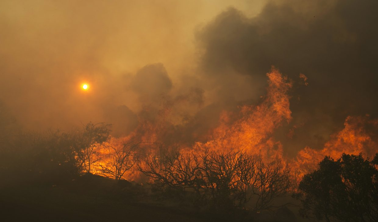 The sun rises as flames from a wildfire burn Monday, Oct. 9, 2017, east of Napa, Calif. The fire is one of several burning across Northern California's wine country.