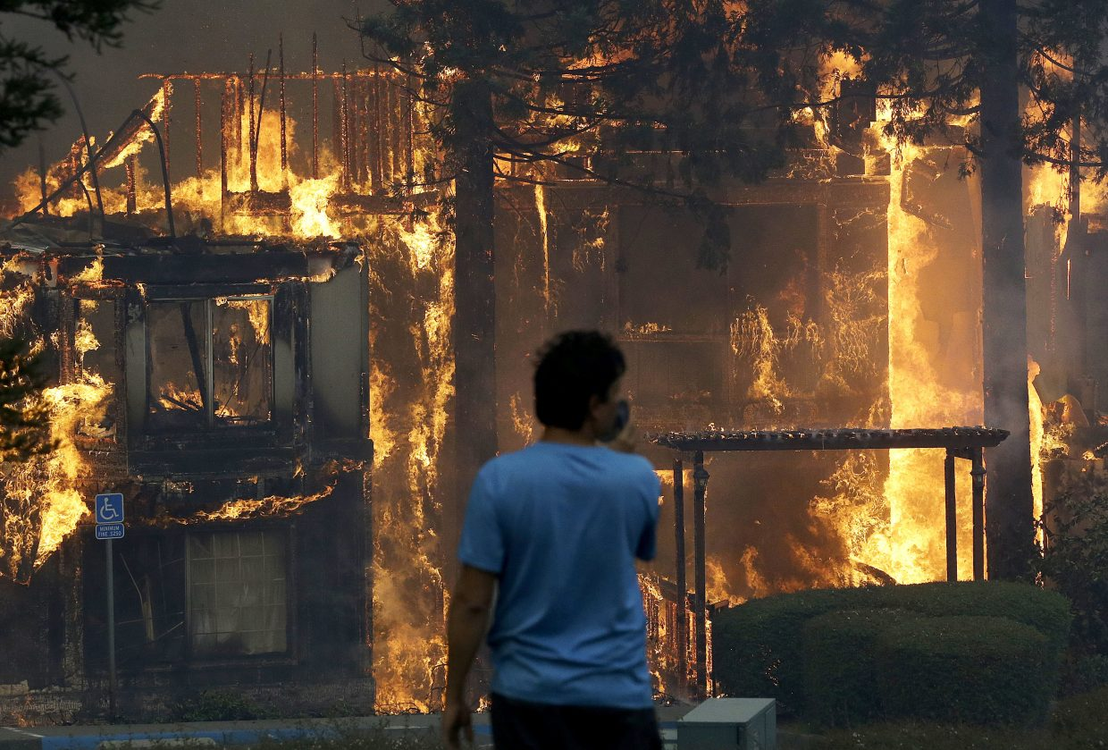 Rudy Habibe, from Puerto Rico, stands by the burning Hilton Sonoma Wine Country hotel, where he was a guest, in Santa Rosa, Calif., Monday, Oct. 9, 2017. Wildfires whipped by powerful winds swept through Northern California, sending residents on a headlong flight to safety through smoke and flames as homes burned.