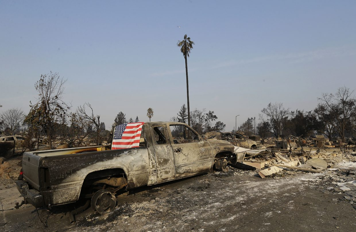 A flag is draped on the back of a truck destroyed by fires in Santa Rosa, Calif., Wednesday, Oct. 11, 2017. Wildfires tearing through California's wine country continued to expand Wednesday, destroying hundreds more homes and structures and prompting new evacuation orders.