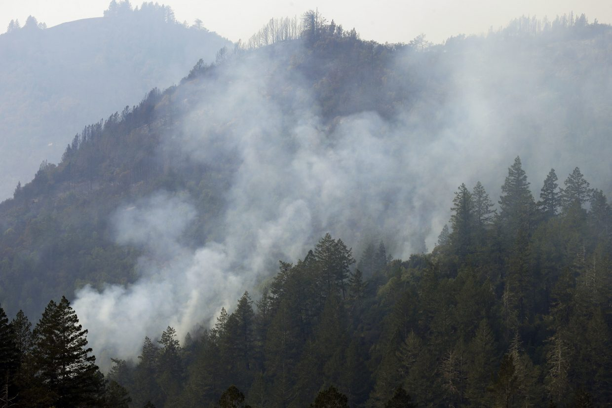 Smoke rises from a wildfire on Wednesday, Oct. 11, 2017 near Calistoga, Calif. The wildfires tearing through California wine country flared anew Wednesday, growing in size and number as authorities issued new evacuation orders and announced that hundreds more homes and businesses had been lost.