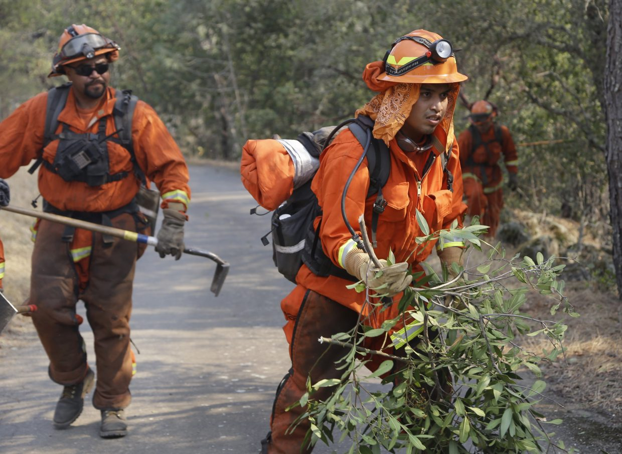 Prisoners from the McCain inmate crew from San Diego, Calif., clear brush from a road on Wednesday, Oct. 11, 2017 in Calistoga, Calif. The wildfires tearing through California wine country flared anew Wednesday, growing in size and number as authorities issued new evacuation orders and announced that hundreds more homes and businesses had been lost.