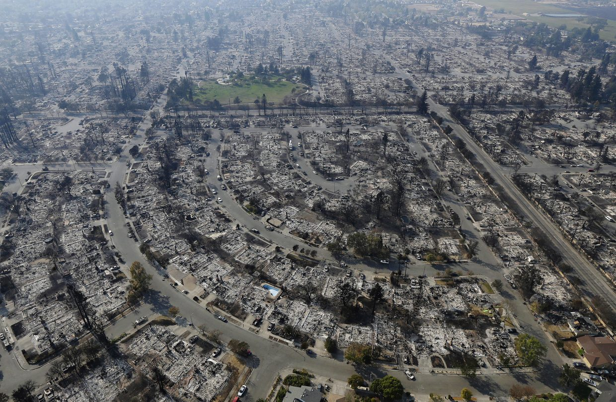 Homes burned by a wildfire are seen Wednesday, Oct. 11, 2017, in Santa Rosa, Calif. Wildfires whipped by powerful winds swept through Northern California sending residents on a headlong flight to safety through smoke and flames as homes burned.