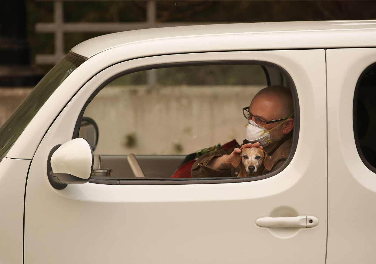 Chris Shiery pets his dog, Ruby, while waiting to evacuate the town of Sonoma, Calif., Wednesday, Oct. 11, 2017. With fires getting near, the town was placed under a voluntary evacuation order.