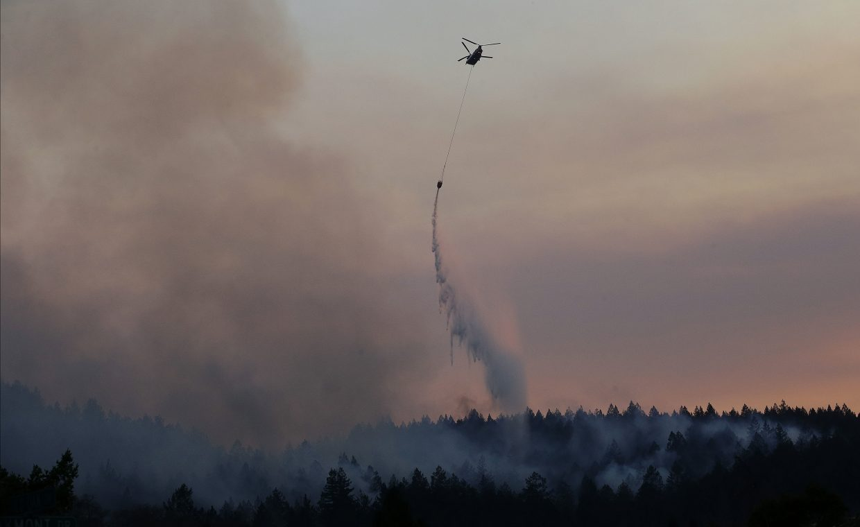 A helicopter drops water on a hill in the Oakmont area in Santa Rosa, Calif., Thursday, Oct. 12, 2017. A forecast for gusty winds and dry air threatened to fan the fires, which were fast becoming the deadliest and most destructive in California history.