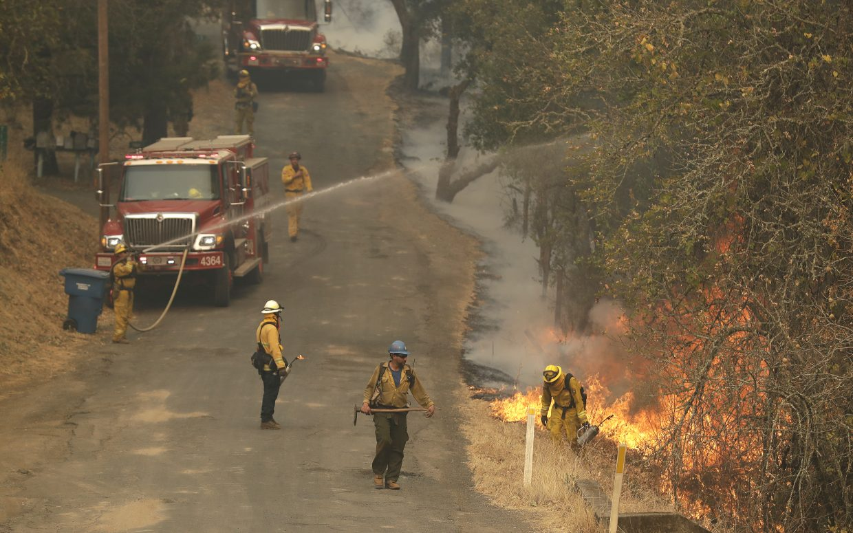 Firefighters set a containment line with a backburn as they battle a wildfire Friday, Oct. 13, 2017, in Glen Ellen, Calif.