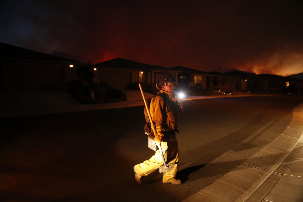 A firefighter looks for flammable items in an evacuated residential area as wildfires continue to burn Saturday, Oct. 14, 2017, in Santa Rosa, Calif. Fire officials have ordered mandatory evacuations.