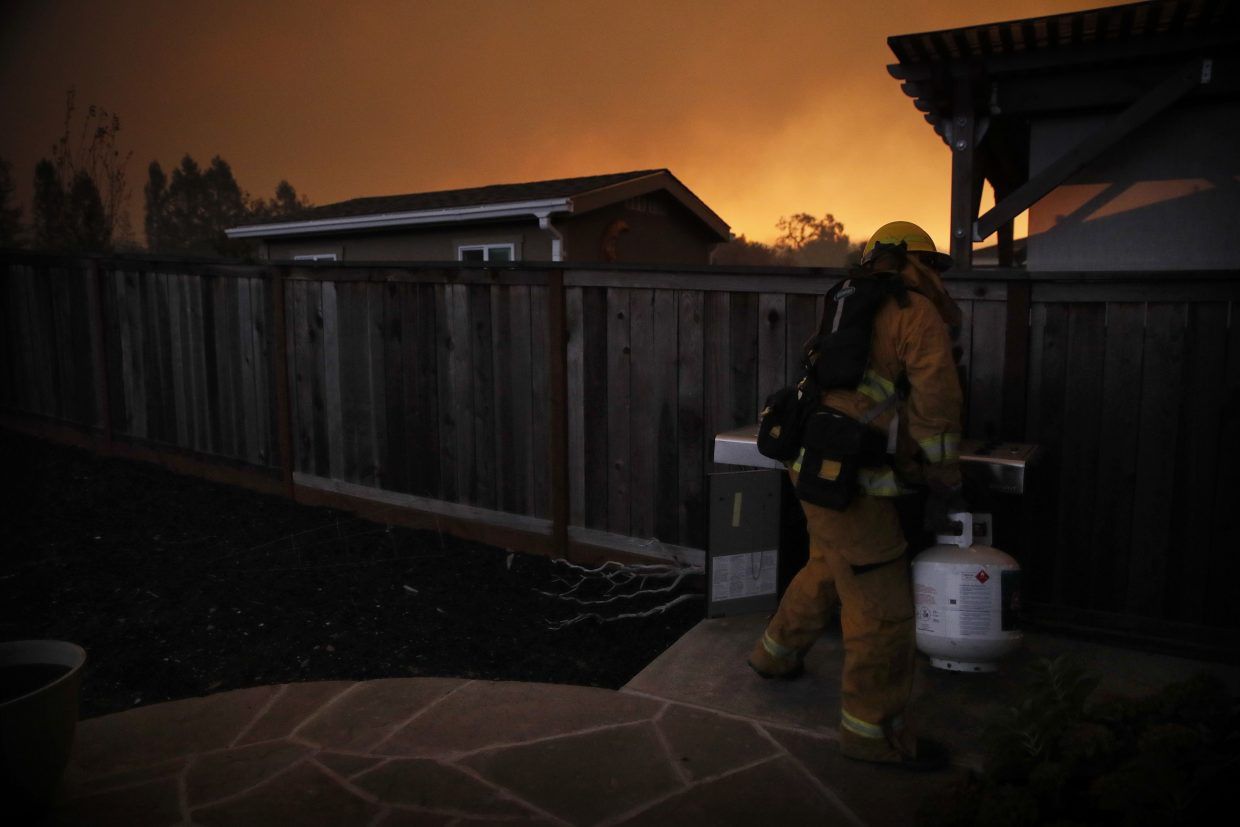 A firefighter removes a propane gas tank in an evacuated residential area as wildfires continue to burn Saturday, Oct. 14, 2017, in Santa Rosa, Calif. The Santa Rosa Fire Department released a notice early Saturday morning, ordering residents in Skyhawk, Mountain Hawk and some of Rincon Valley to leave their homes.