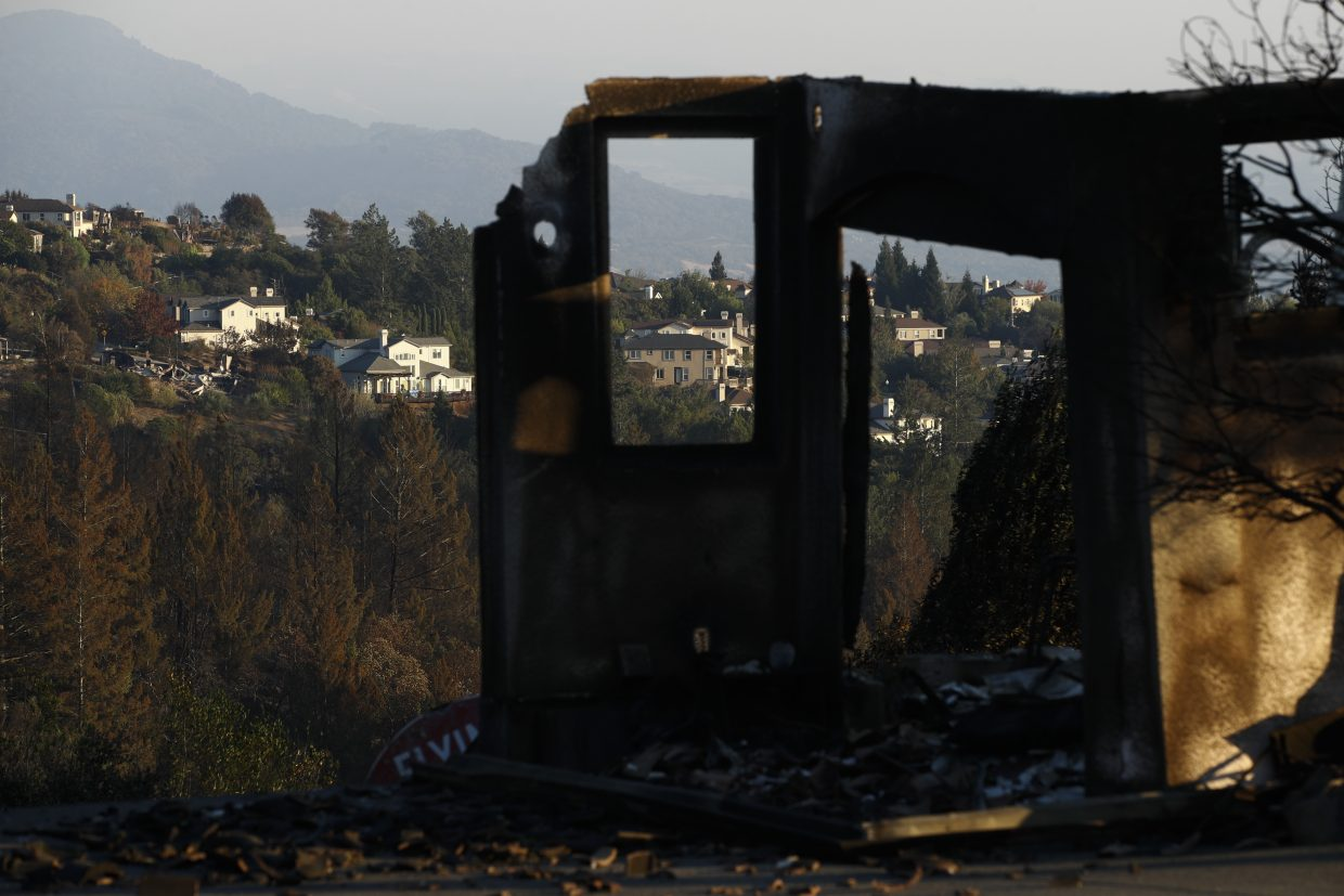 Homes are seen through a house destroyed by a wildfire Saturday, Oct. 14, 2017, in Santa Rosa, Calif. Nearly a week after the blazes began, the fires have left dozens of people dead and destroyed thousands of homes and businesses, making them the deadliest and most destructive group of wildfires in California history.