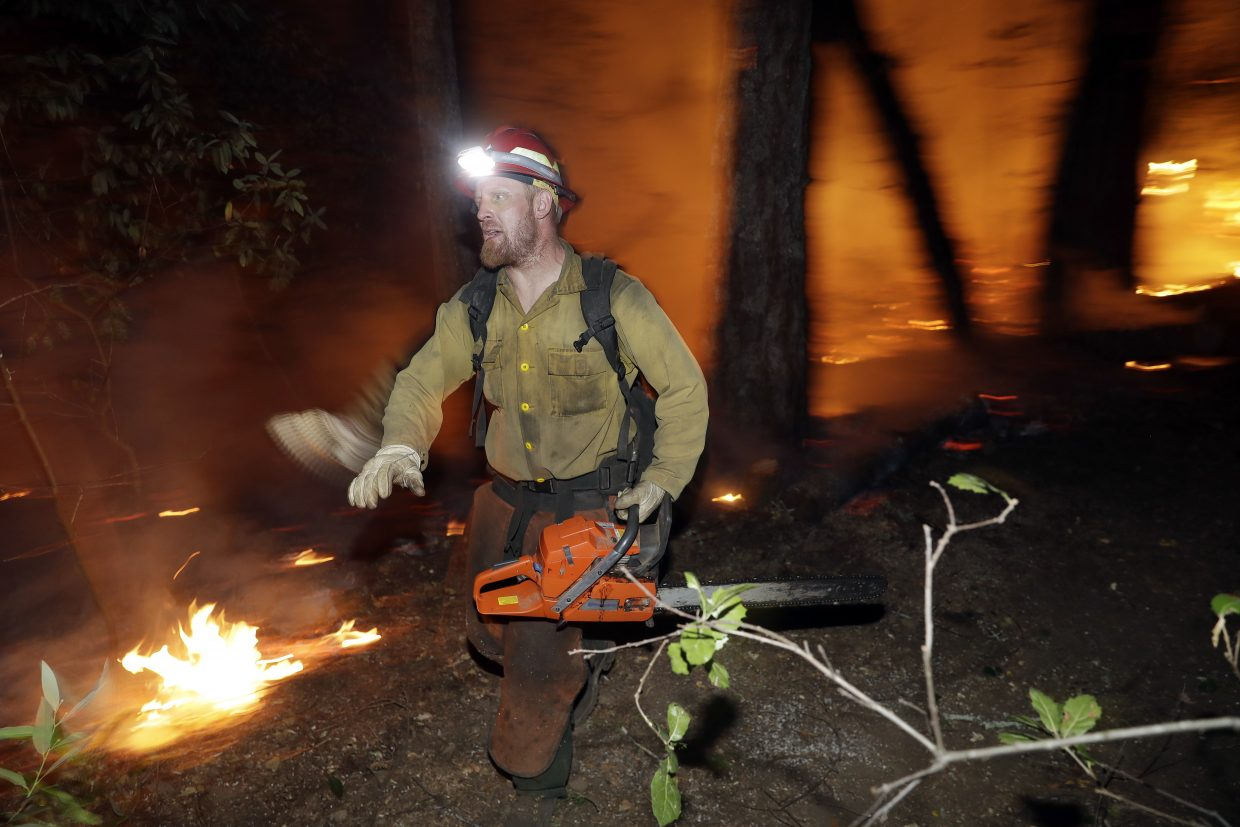 A firefighter runs along a containment line while battling a wildfire Saturday, Oct. 14, 2017, in Santa Rosa, Calif.