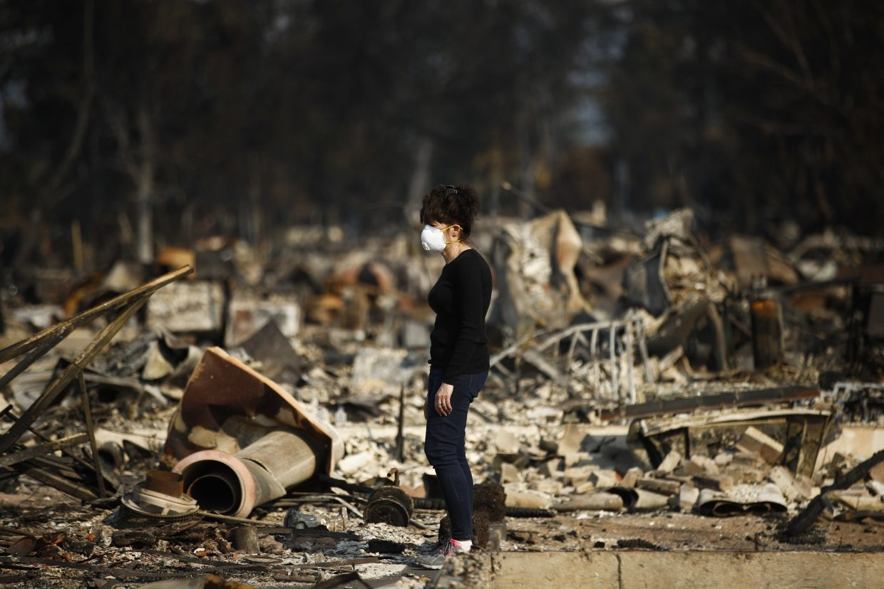Karen Curzon stands in what remains of her home, which was destroyed by a wildfire in the Coffey Park neighborhood, Sunday, Oct. 15, 2017, in Santa Rosa, Calif.