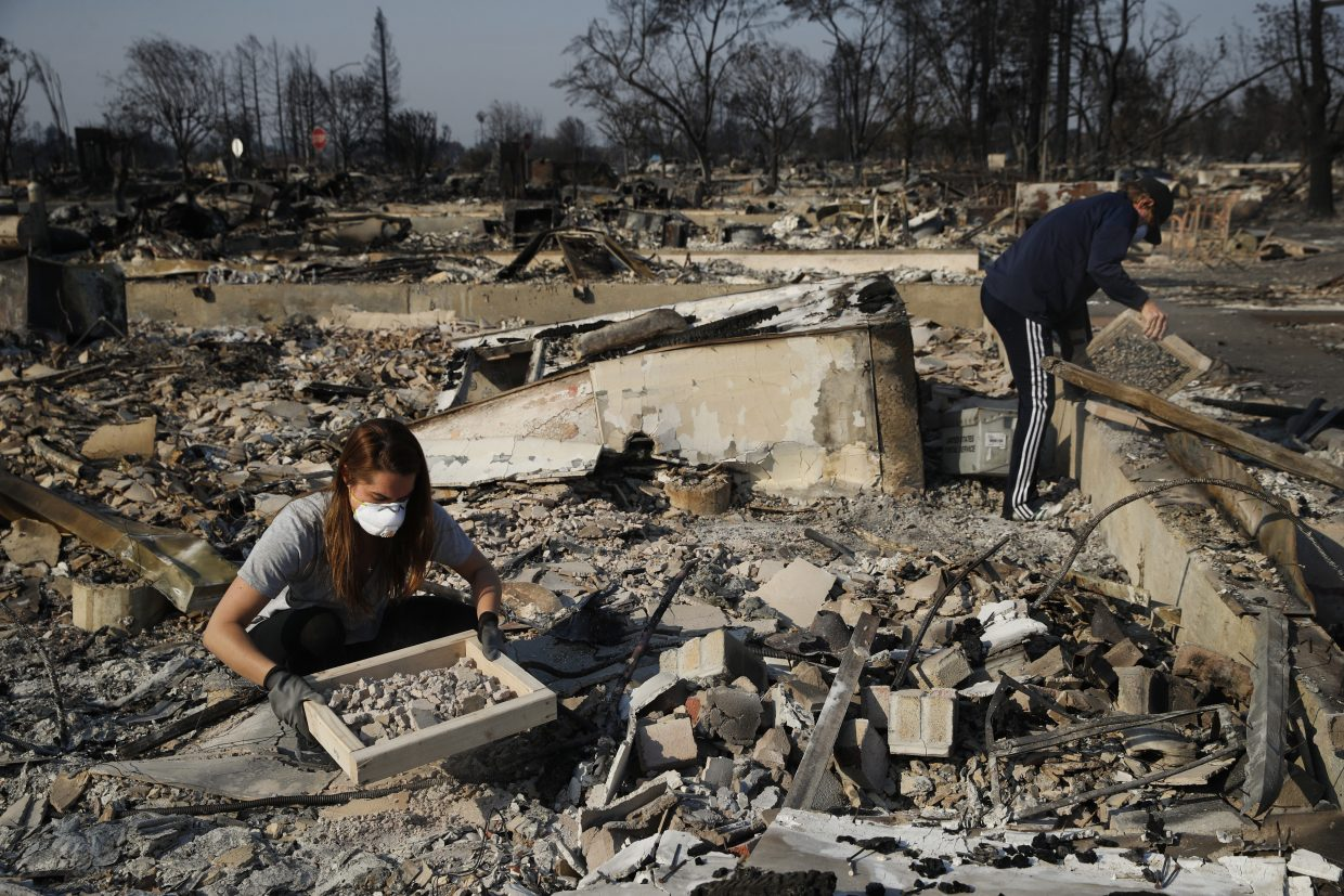 Ed Curzon, right, and his daughter Margaret sift debris to salvage anything they can from the rubble of their home, destroyed by a wildfire in the Coffey Park neighborhood Sunday, Oct. 15, 2017, in Santa Rosa, Calif.