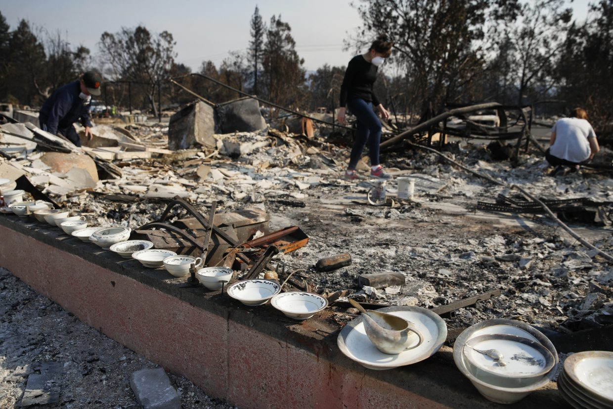 A set of salvaged china that Karen Curzon, background center, inherited from her grandmother lie on the foundation of her home that was destroyed by a wildfire in the Coffey Park neighborhood Sunday, Oct. 15, 2017, in Santa Rosa, Calif.