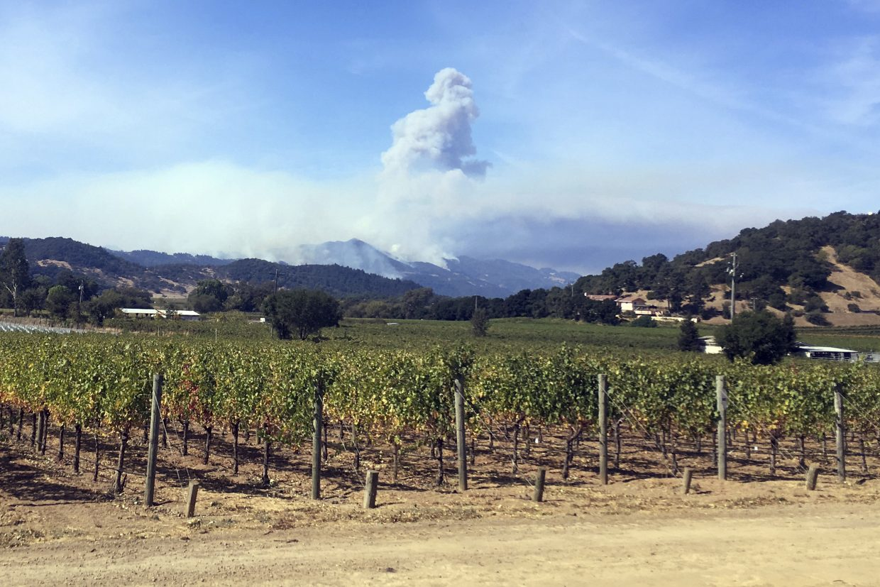 Smoke continues to billow in the hills behind Napa, Calif., on Sunday, Oct. 15, 2017. With the winds dying down, fire officials said Sunday they were finally getting the upper hand against the wildfires that have devastated California wine country and other parts of the state over the past week, and thousands of people got the all-clear to return home.