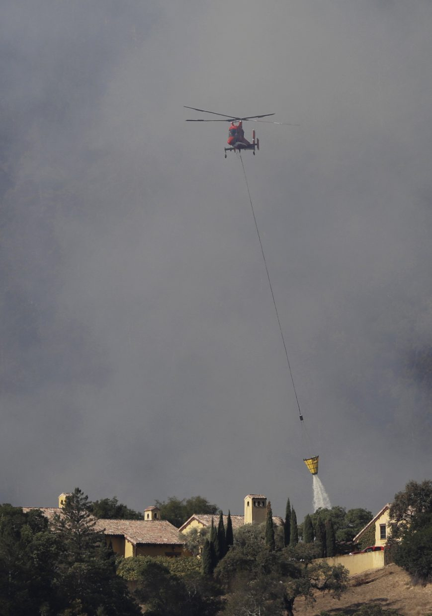 A helicopter drops water over a property as smoke rises from a wildfire, Sunday, Oct. 15, 2017, in Oakville, Calif. With the winds dying down, fire officials in California say they are finally getting the upper hand against the wildfires that have devastated wine country and other parts of the state over the past week.