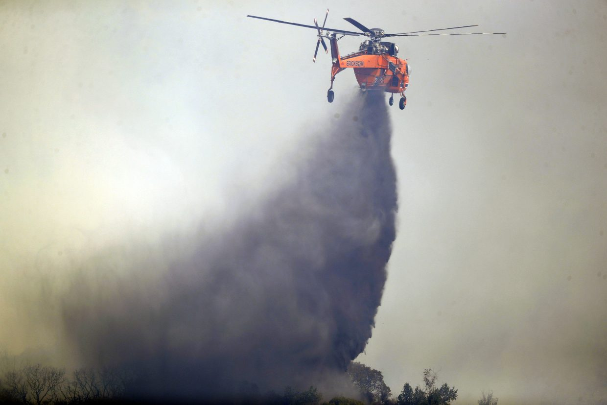 A helicopter drops water onto a burning wildfire, Sunday, Oct. 15, 2017, in Oakville, Calif. With the winds dying down, fire officials in California say they are finally getting the upper hand against the wildfires that have devastated wine country and other parts of the state over the past week.