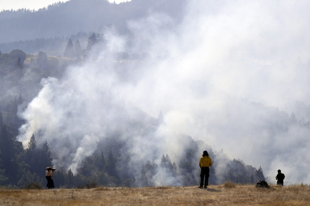 A firefighter, center, and two onlookers watch a smoldering wildfire from a hilltop, Sunday, Oct. 15, 2017, in Oakville, Calif. With the winds dying down, fire officials in California say they are finally getting the upper hand against the wildfires that have devastated wine country and other parts of the state over the past week.