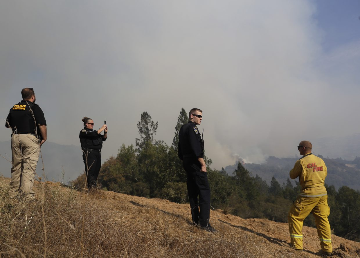 Firefighters and police officers view a burning wildfire, Sunday, Oct. 15, 2017, in Oakville, Calif. With the winds dying down, fire officials in California say they are finally getting the upper hand against the wildfires that have devastated wine country and other parts of the state over the past week.