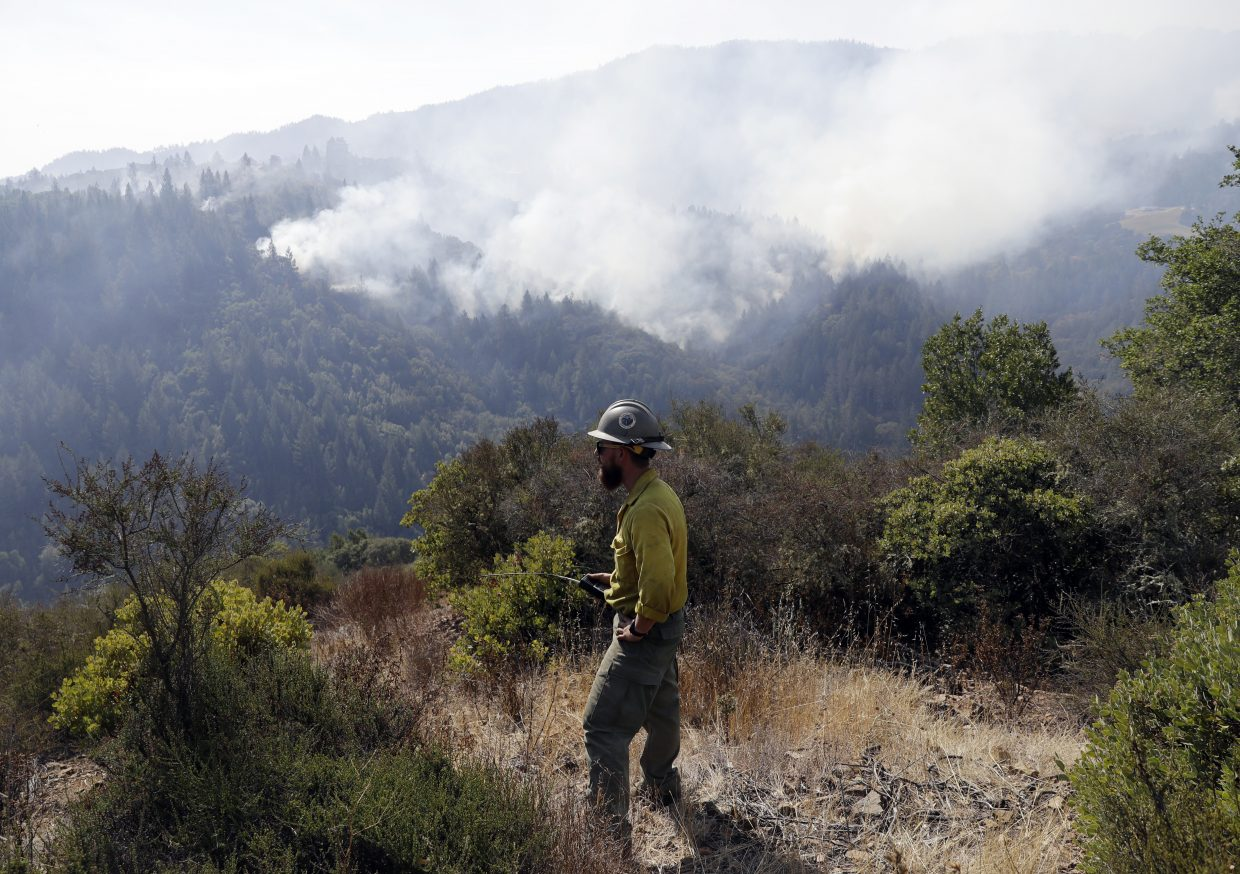 Jeff Wolf, with the El Dorado Hot Shots, out of Pollock Pines, Calif., monitors a wildfire from a mountain top, Sunday, Oct. 15, 2017, in Oakville, Calif. With the winds dying down, fire officials in California say they are finally getting the upper hand against the wildfires that have devastated wine country and other parts of the state over the past week.