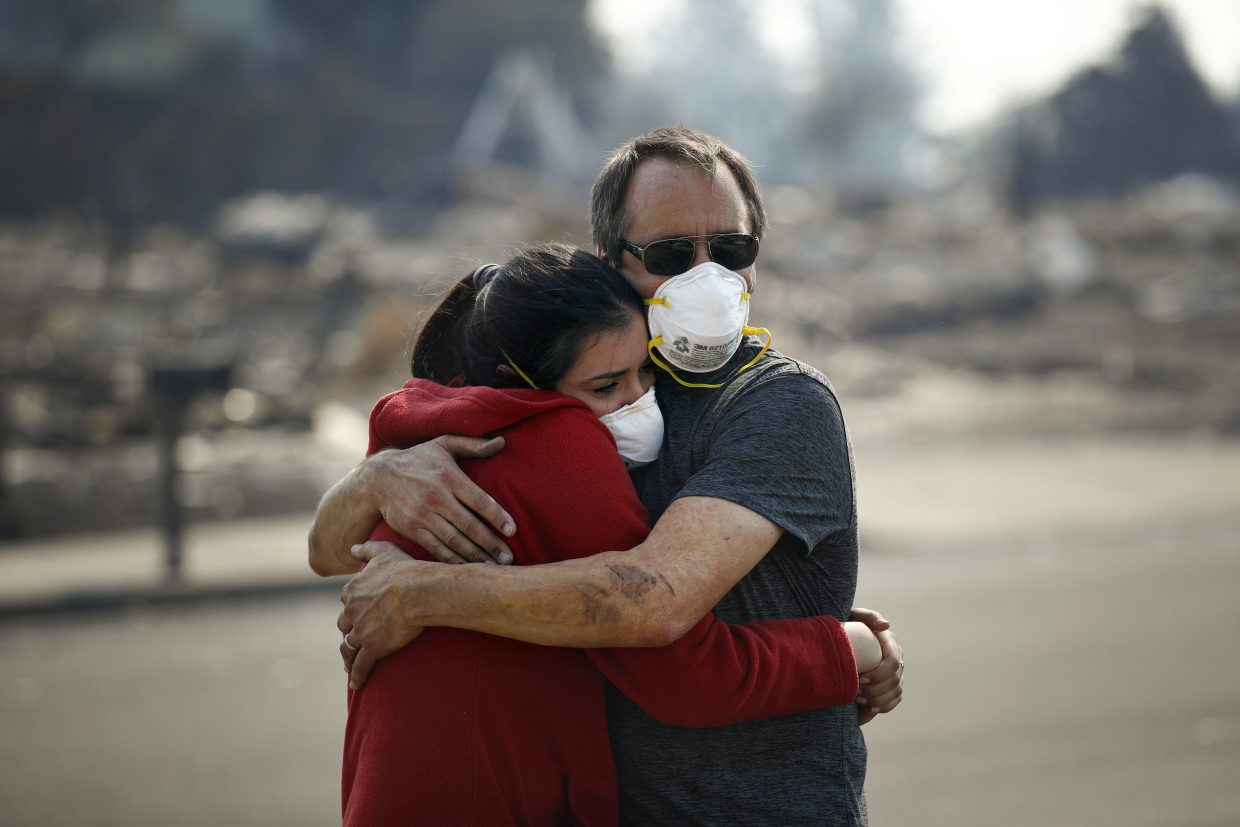 Howard Lasker, right, comforts his daughter, Gabrielle, who is visiting their home for the first time since a wildfire swept through it Sunday, Oct. 15, 2017, in Santa Rosa, Calif. With the winds dying down, fire officials said Sunday they have apparently