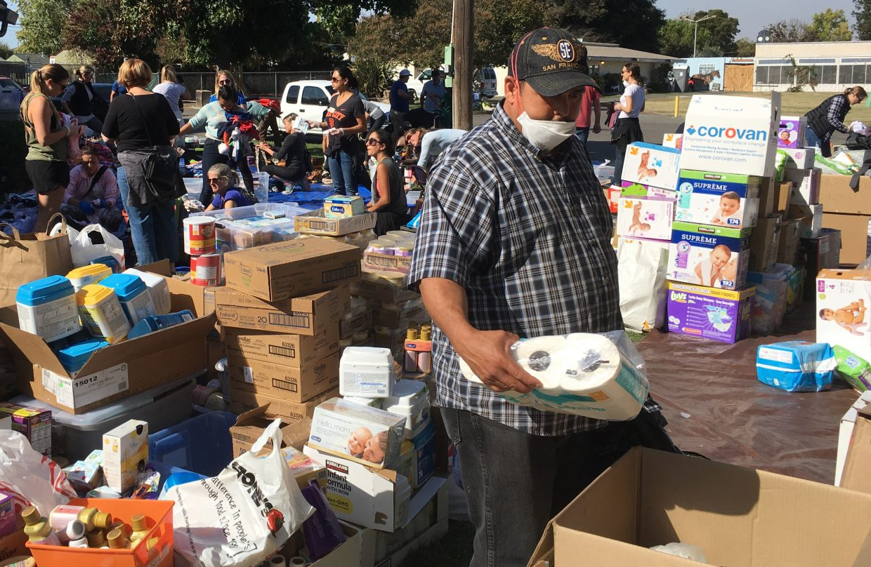Wildfire evacuee Gonzalo Jauregui, a local grape picker, browses through donated toiletries at the Sonoma-Marin Fairgrounds in Petaluma, Calif., Sunday, Oct. 17, 2017. Fall is harvest time in Northern California. And while some are gathering the last grapes from vineyards, others are still searching for lost loved ones or planning memorial services for those who died. So many ordinary busy lives have now slipped off track, grossly interrupted by a weeklong complex of historically destructive wildfires that have killed dozens of people and destroyed more than 5,000 homes and structures.