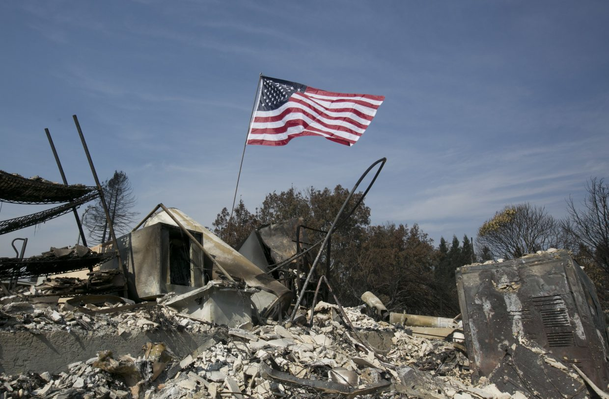 A United States flag flies over the charred remains of a house in the Coffey Park area of Santa Rosa, Calif., Monday, Oct. 16, 2017.