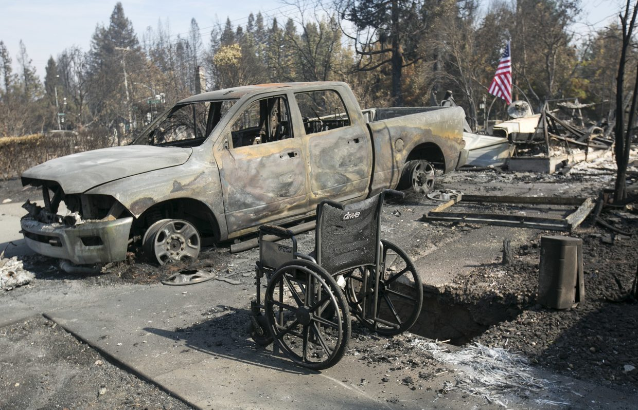A scorched truck and wheelchair sit outside the charred remains of a house in the Coffey Park area of Santa Rosa, Calif., Monday, Oct. 16, 2017.