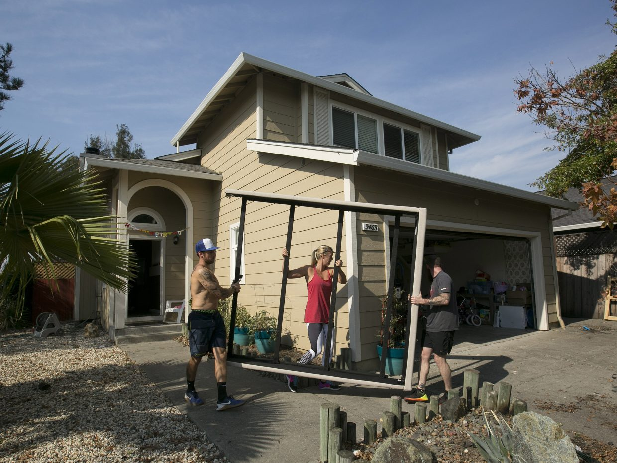 Chris Alejos, left, and his wife, Brittany, get help from friend Nick Cann as they remove a bed frame from their home in the Coffey Park area of Santa Rosa, Calif. Monday, Oct. 16, 2017. The Alejos home was not damaged by the fire that destroyed homes all around theirs, but smoke damage and no power made it unlivable for now.