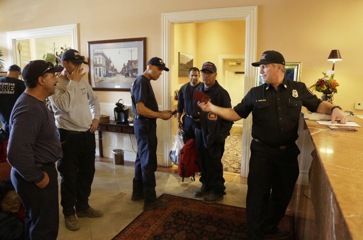 Firefighters from Southern California wait to check into their rooms at the Napa River Inn, Monday, Oct. 16, 2017, in Napa, Calif. First responders have been allowed to stay free at the hotel all week. With the winds dying down, fire crews gained ground as they battled wildfires that have devastated California wine country and other parts of the state over the past week, and thousands of people got the all-clear to return home.