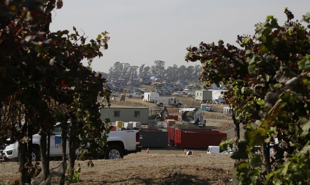 A Pacific Gas and Electric base camp is visible in the distance at Starmont Winery and Vineyards, Monday, Oct. 16, 2017, in Napa, Calif. With the winds dying down, fire crews gained ground as they battled wildfires that have devastated California wine country and other parts of the state over the past week, and thousands of people got the all-clear to return home.