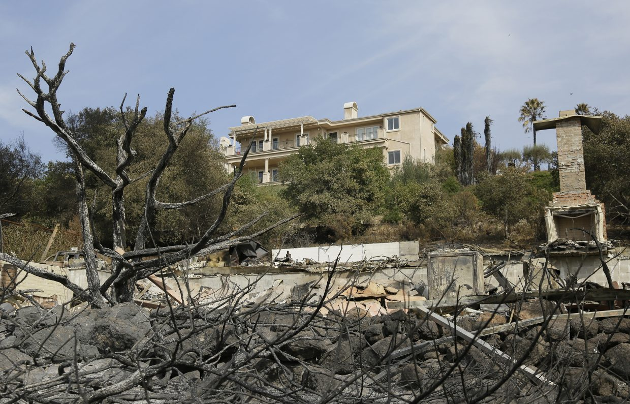A house stands intact above one that was destroyed by wildfire near Atlas Peak Road, Monday, Oct. 16, 2017, in Napa, Calif. State and local officials say they are trying to get people back into their homes, but they cautioned that it could take days and even weeks for neighborhoods hard hit by Northern California wildfires.