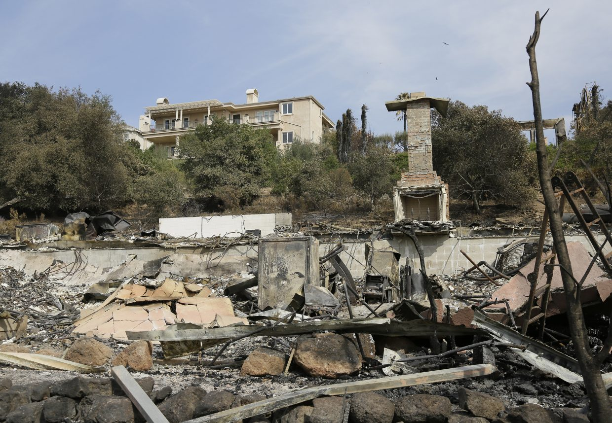 A house stands intact above one that was destroyed by wildfire near Atlas Peak Road Monday, Oct. 16, 2017, in Napa, Calif. State and local officials say they are trying to get people back into their homes, but they cautioned that it could take days and even weeks for neighborhoods hard hit by Northern California wildfires.