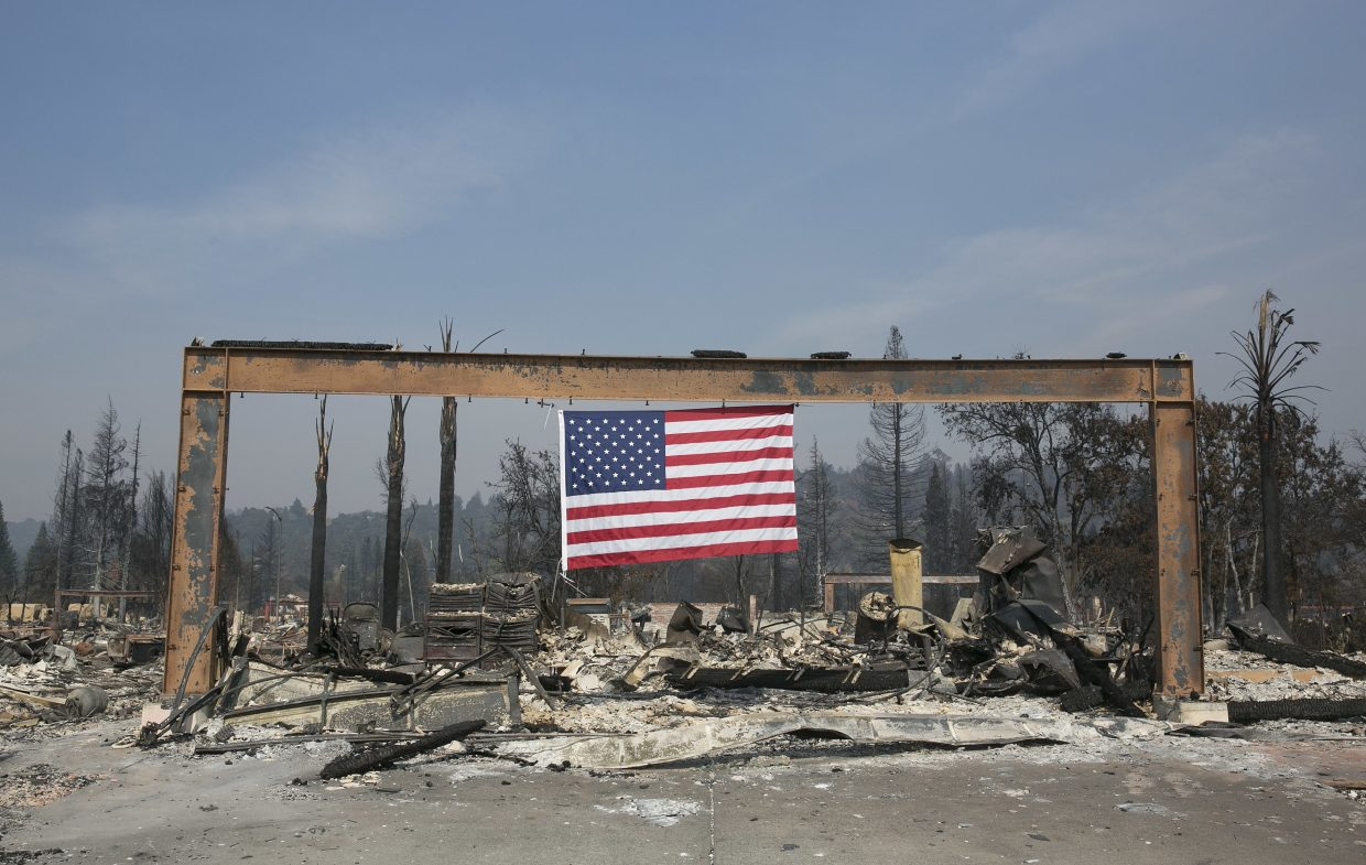 A United States flag hangs from the charred remains of a home in Santa Rosa, Calif. Monday, Oct. 16, 2017. Massive wildfires swept through area last week destroying thousands of homes and businesses and claiming the lives of dozens of people who were unable to escape the flames.