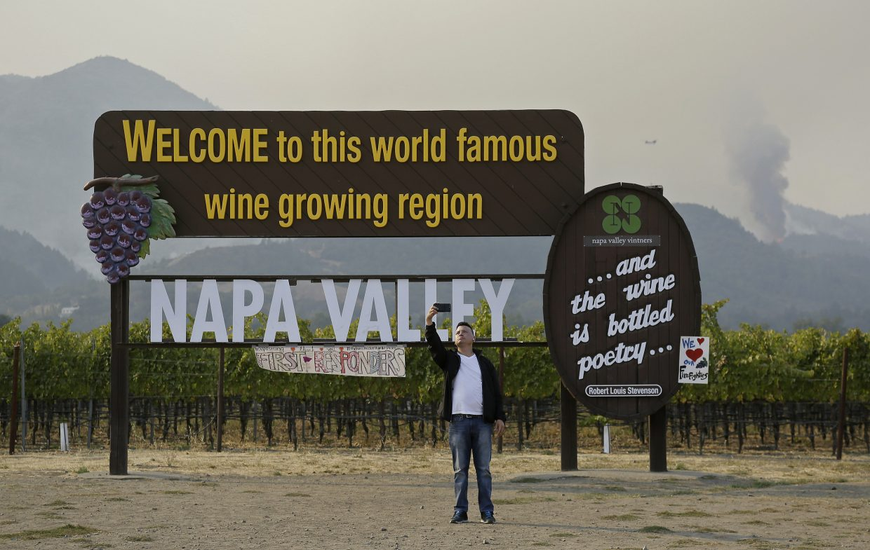 A man stops to take a photo by the Welcome to the Napa Valley sign as the Nuns wildfire burns in the background Monday, Oct. 16, 2017, in Oakville, Calif. State and local officials say they are trying to get people back into their homes, but they cautioned that it could take days and even weeks for neighborhoods hard hit by Northern California wildfires.