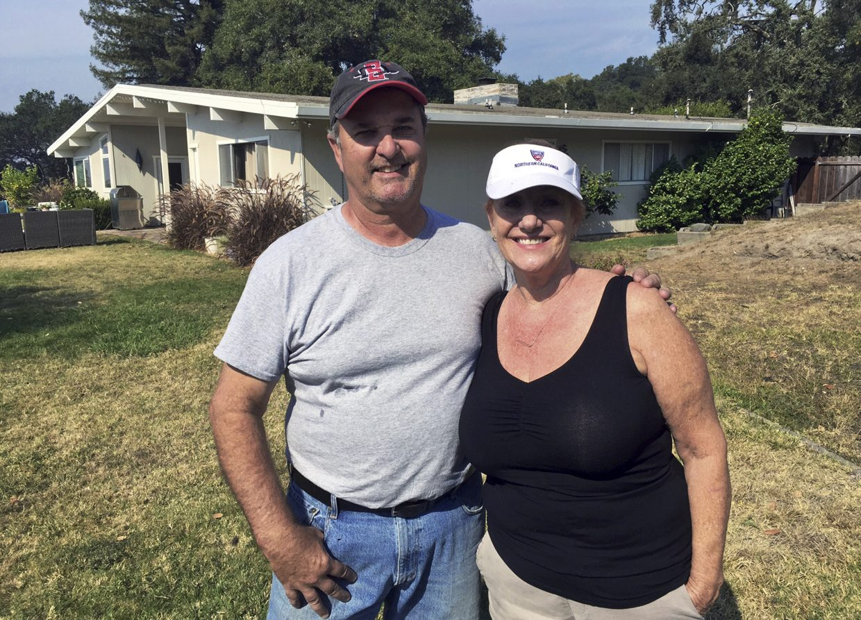 Tom and Catherine Andrews pose at their home in Santa Rosa, Calif., Monday, Oct. 16, 2017. They live on the edge of devastation. On one side of their mid-century style home, the deadly wildfires that ravaged parts of Northern California for more than a week wiped away the houses of neighbors they have known as long as two decades. On the other side, were those like the Andrews, who were spared.